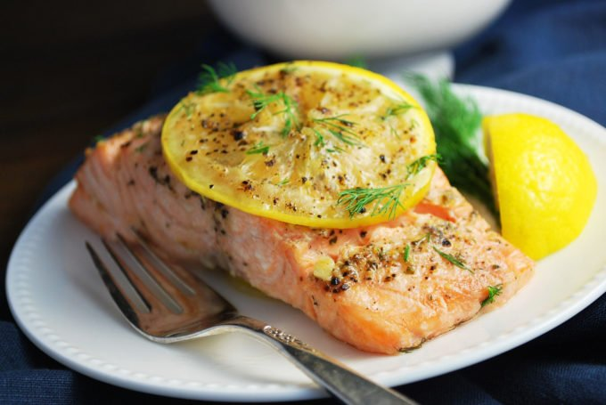 close up picture of a grilled salmon filet topped with lemon and herbs