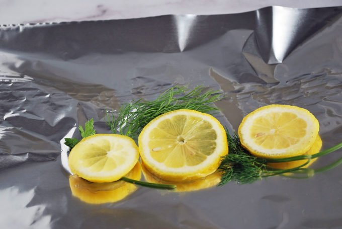 Lemon slices and herbs on top of aluminum foil
