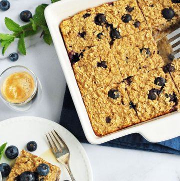 Blueberry baked oatmeal in a dish with a plate and berries