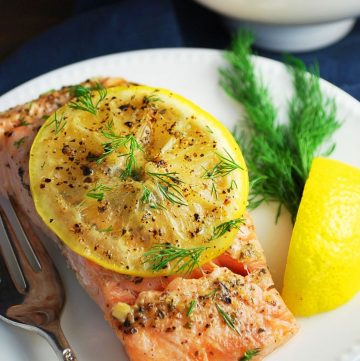 plate of salmon with a lemon wedge and herbs