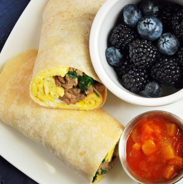 meal prep burritos on a plate with berries and salsa