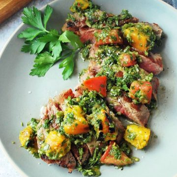 plate of sliced strip steak with peach chimichurri on top