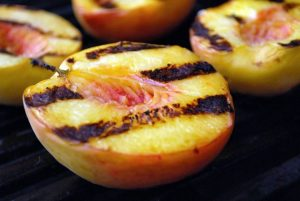 Grilled peach halves on a gas grill