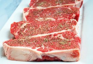 Raw New York strip steaks seasoned with salt and pepper on a platter