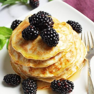 oat flour blender pancakes on a plate with berries and fork