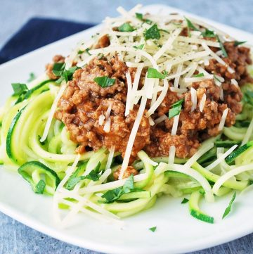 plate of zucchini noodles topped with bolognese sauce and cheese