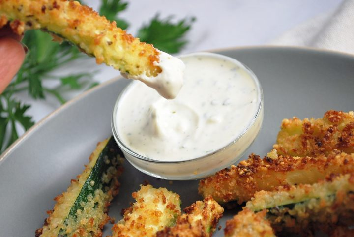 dipping a zucchini fry in yogurt sauce
