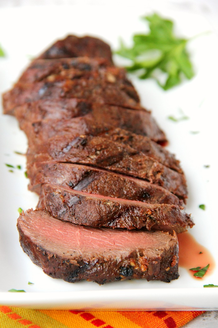 grilled venison backstrap sliced on a platter with fresh herbs