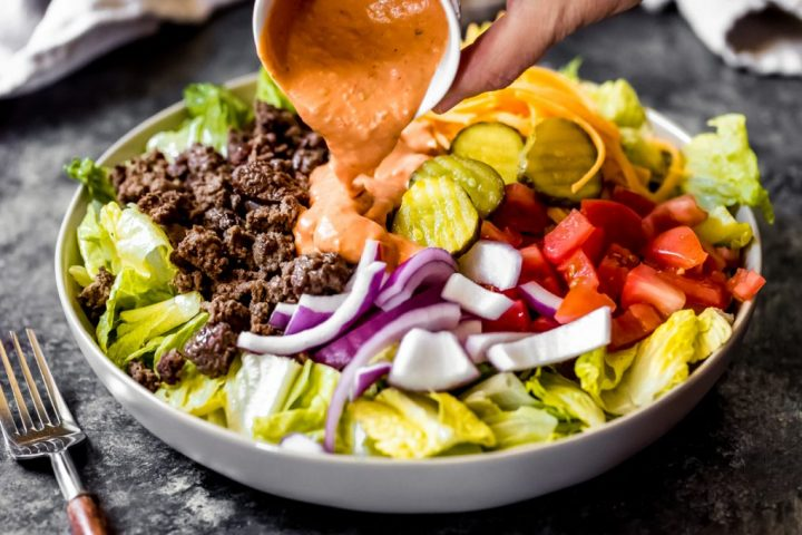 ground venison salad with pickles, tomatoes, and onions with dressing poured on top