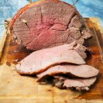 roasted venison on a cutting board sliced