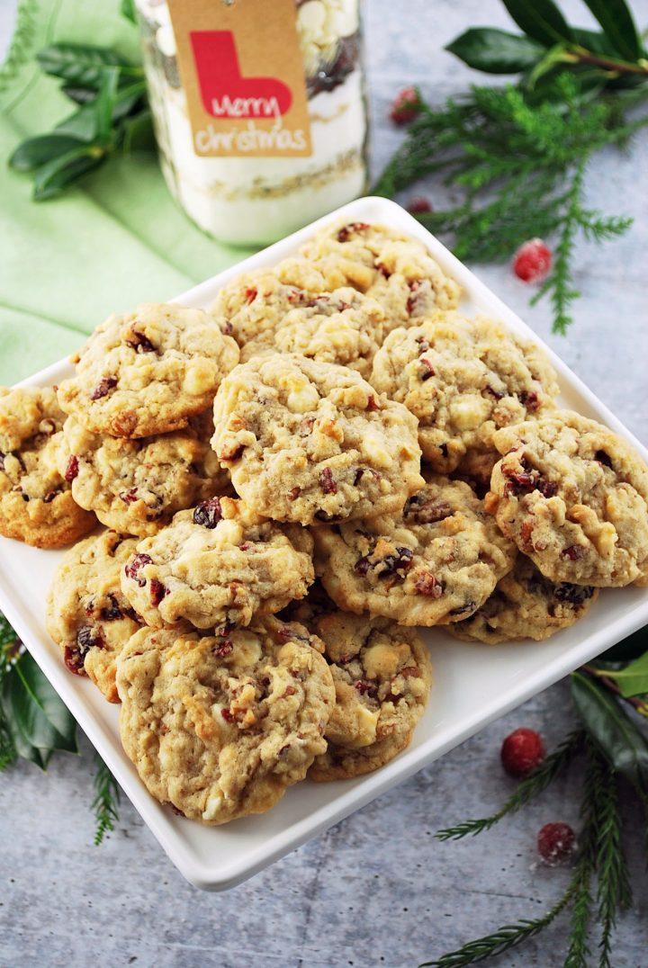cookies on a white platter with holly and berries in the background