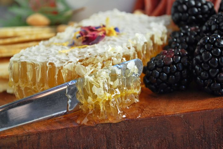 slicing into a honeycomb on a charcuterie board
