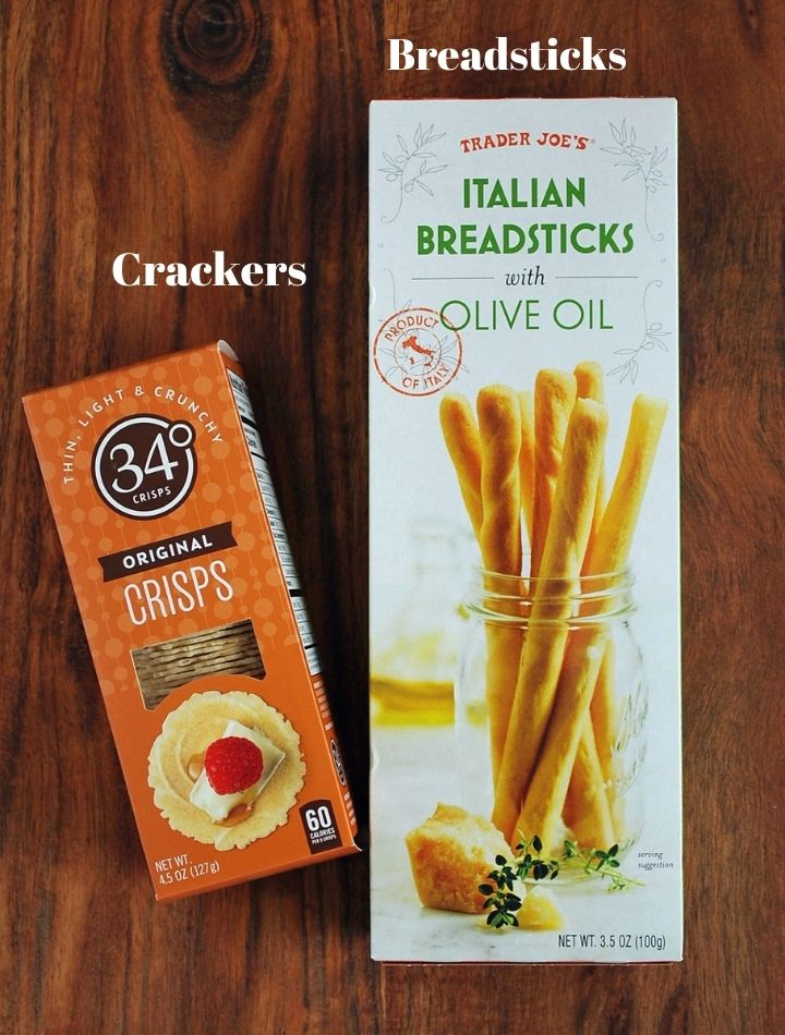 crackers and breadsticks for charcuterie on a cutting board
