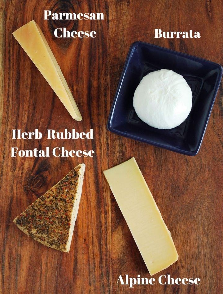 four different cheese varieties for Italian charcuterie on a cutting board