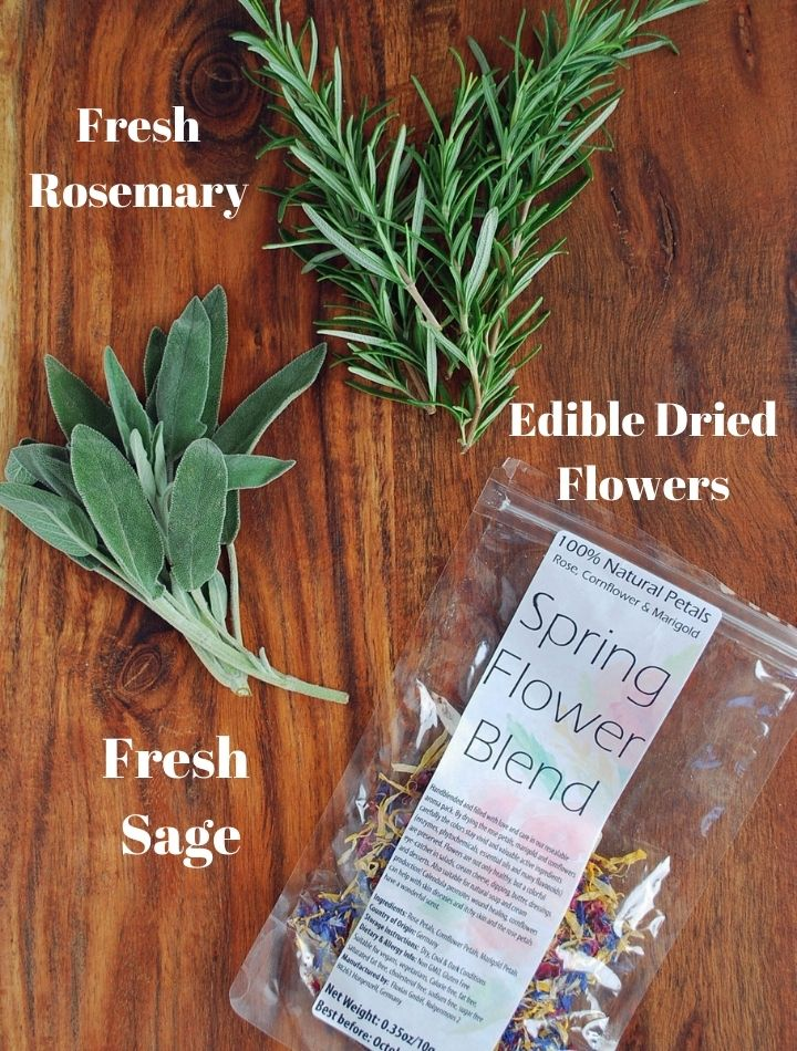 fresh herbs and dried edible flowers on a cutting board