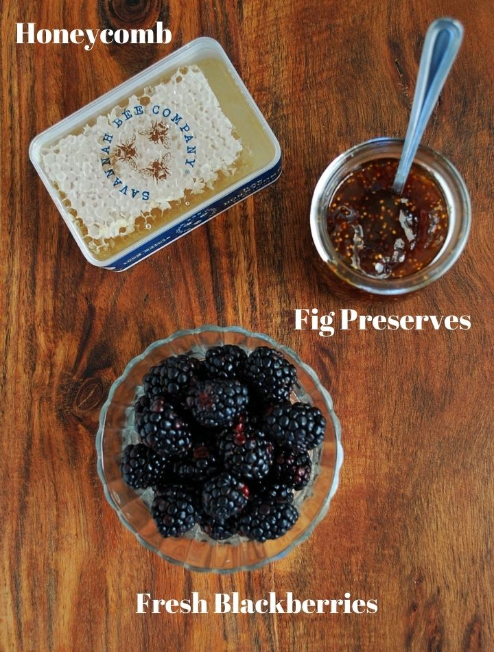 blackberries, fig preserves, and honeycomb for charcuterie on a cutting board
