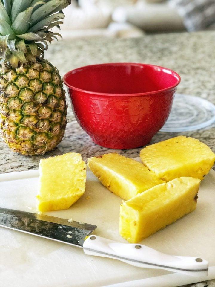 slicing a fresh pineapple on a cutting board