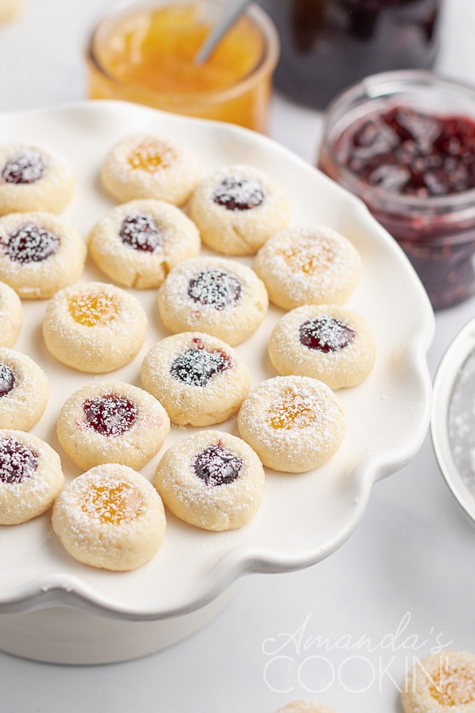 jam filled thumbprint cookies on a platter with jam in background