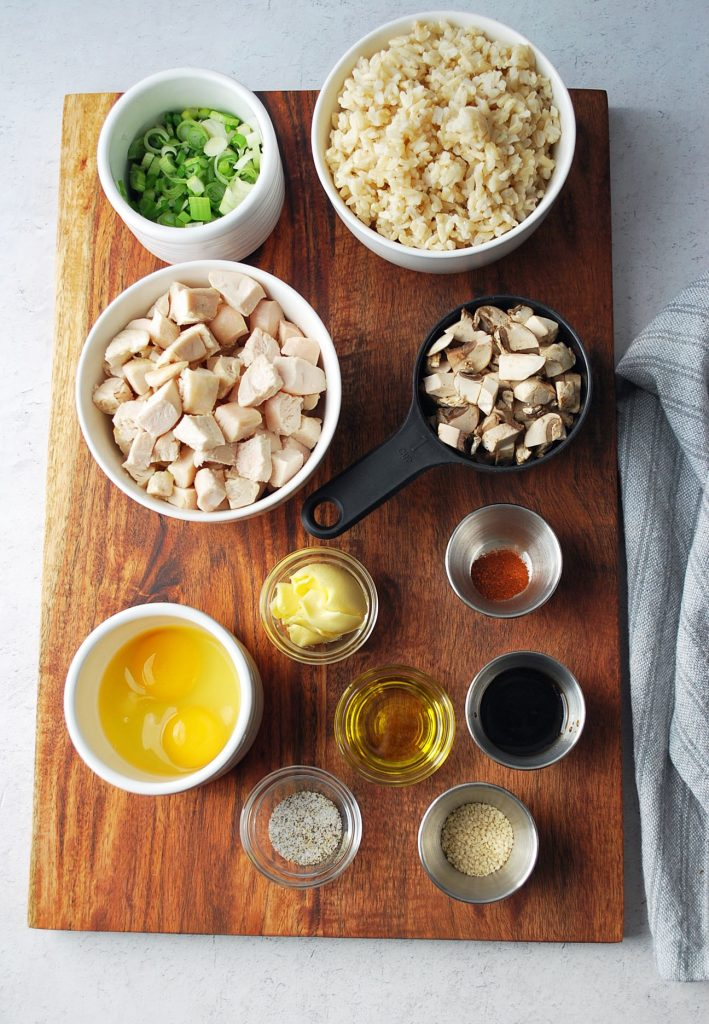 ingredients for chicken fried rice in bowls on top of a wooden cutting board