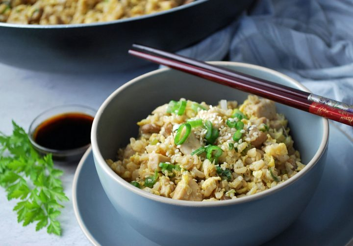 fried rice in a grey bowl with green onions and sesame seeds on top with chopsticks laying on top of the bowl and sauce and a skillet in the background