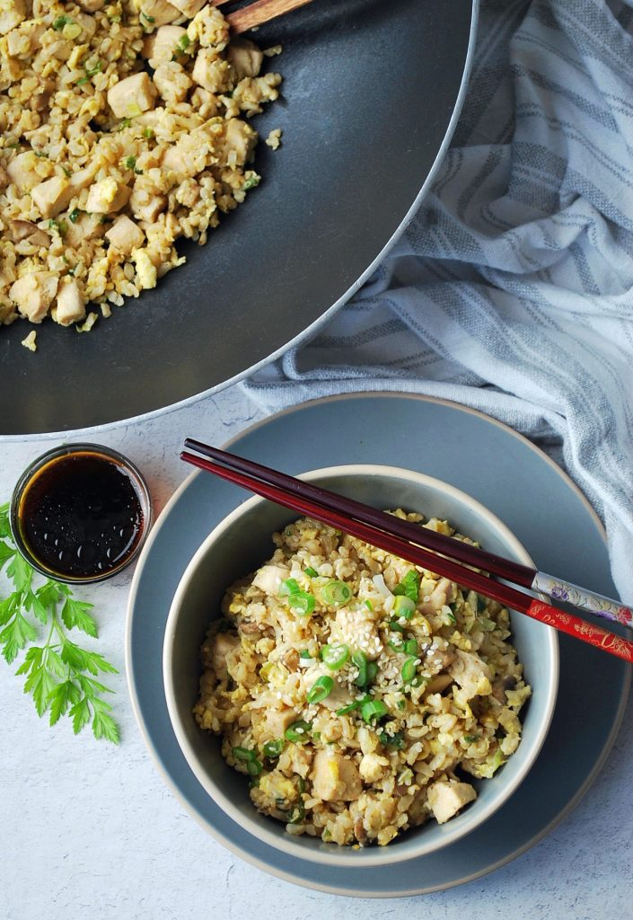 overhead photo of a skillet of fried rice with a bowl of fried rice with chopsticks in the front. There is also a dish of soy sauce and a sprig of parsley on the side