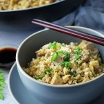 Close up of a bowl of fried rice with chopsticks laying on top