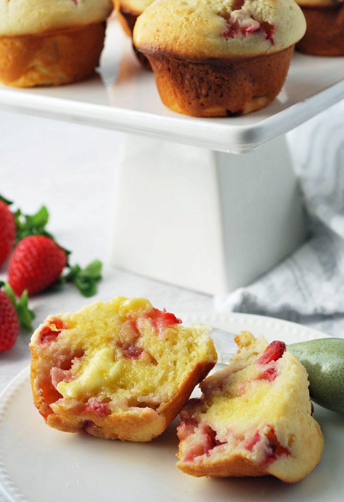 close up photo of a plate with a sliced buttered muffin on top with a butter knife
