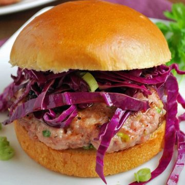 juicy pork burger patty topped with shredded red cabbage and sliced green onions on a brioche bun on a white plate