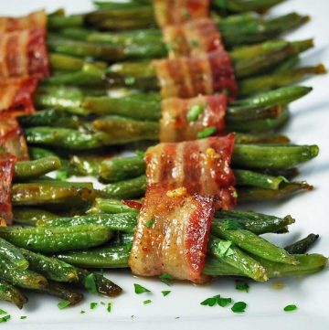 close up photo of cooked bacon-wrapped green beans on a platter with chopped parsley on top