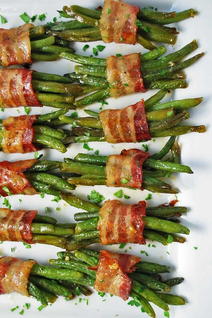 overhead photo of green bean bundles made with bacon and garnished with fresh parsley