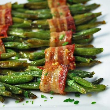 Close up photo of roasted green bean bacon bundles on a white platter with a napkin and fork on the side