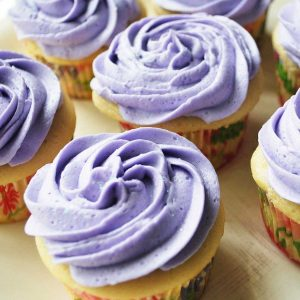 close up of a plate of cupcakes topped with lavender swirled frosting