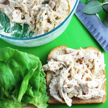 Open-faced chicken salad sandwich on wheat bread with a knife, fresh sage leaves, and a bowl of chicken salad in the background