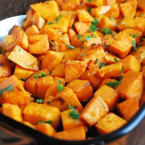 close up photo of roasted sweet potatoes topped with fresh parsley in a casserole dish