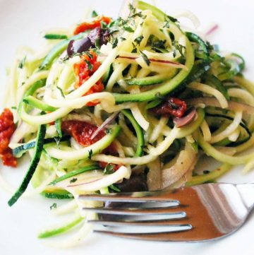 close up of a spiralized zucchini salad with olives and sun-dried tomatoes