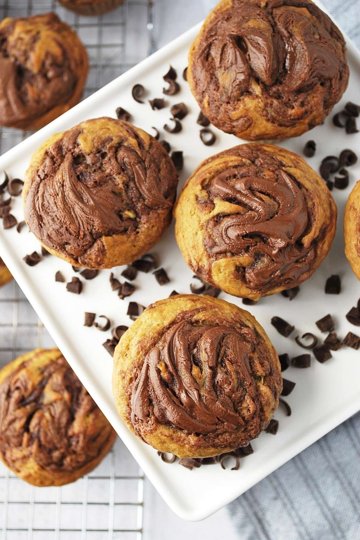 overhead photo of banana nutella muffins on a platter with chocolate shavings