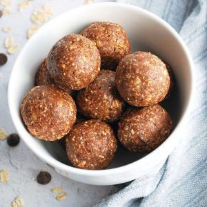 close up of chocolate protein date balls in a white bowl