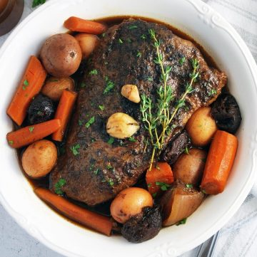 overhead photo of pot roast in a white serving dish with carrots, potatoes, and fresh thyme