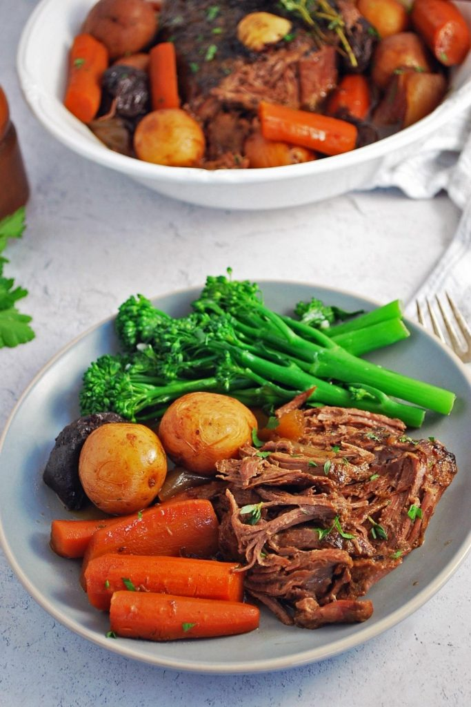 A plate of pot roast with carrots and potatoes and a side of broccolini