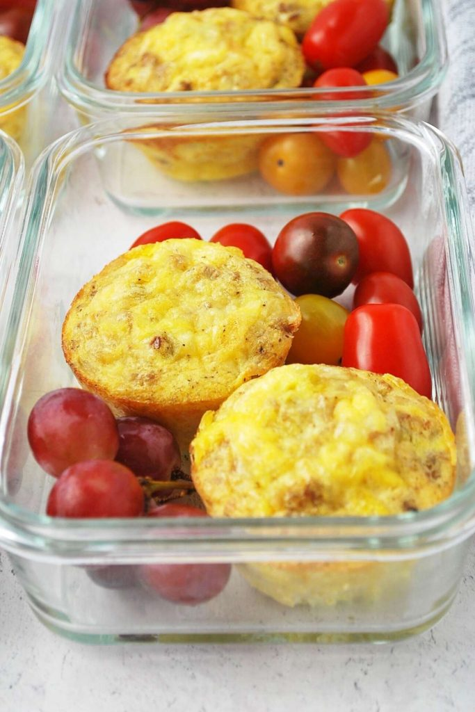 egg muffins with tomatoes and grapes in glass meal prep containers