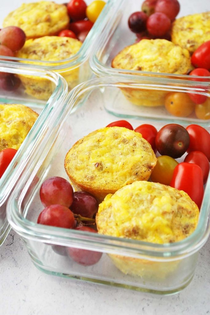 sausage egg muffins in meal prep containers with grapes and tomatoes