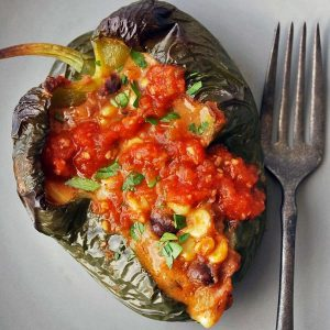 a vegetarian stuffed poblano pepper on a plate topped with salsa
