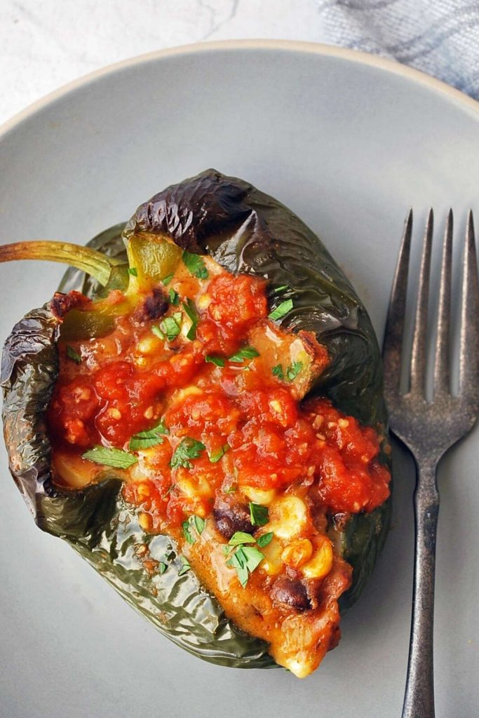 stuffed poblano pepper topped with salsa on a plate with a fork