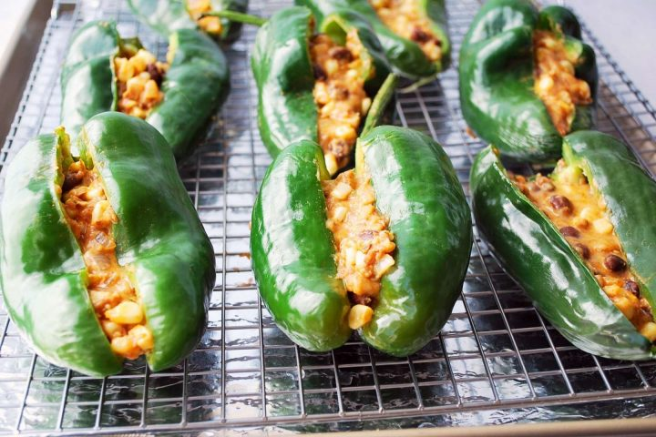 poblano peppers stuffed with a vegetarian filling on a baking rack ready to cook