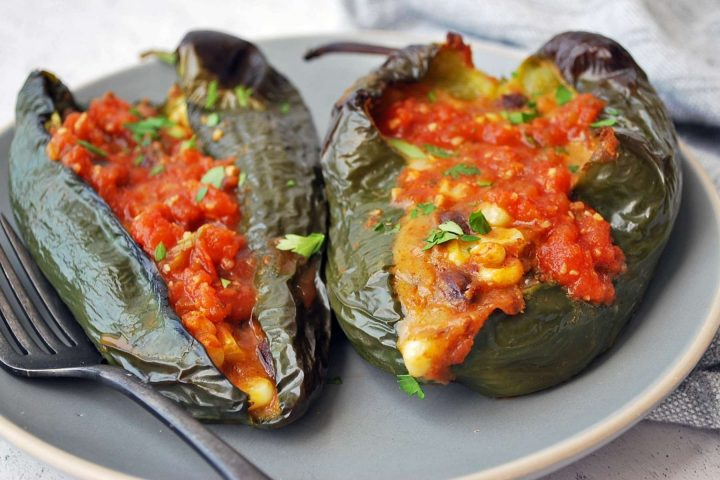 Two stuffed poblano peppers on a plate with a fork