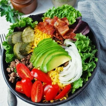 close up of a California burger bowl topped with avocado, tomatoes, pickles, bacon, onions, and cheese