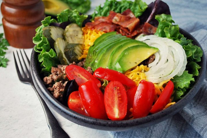 side view of California burger bowl with all the toppings and a fork on the side