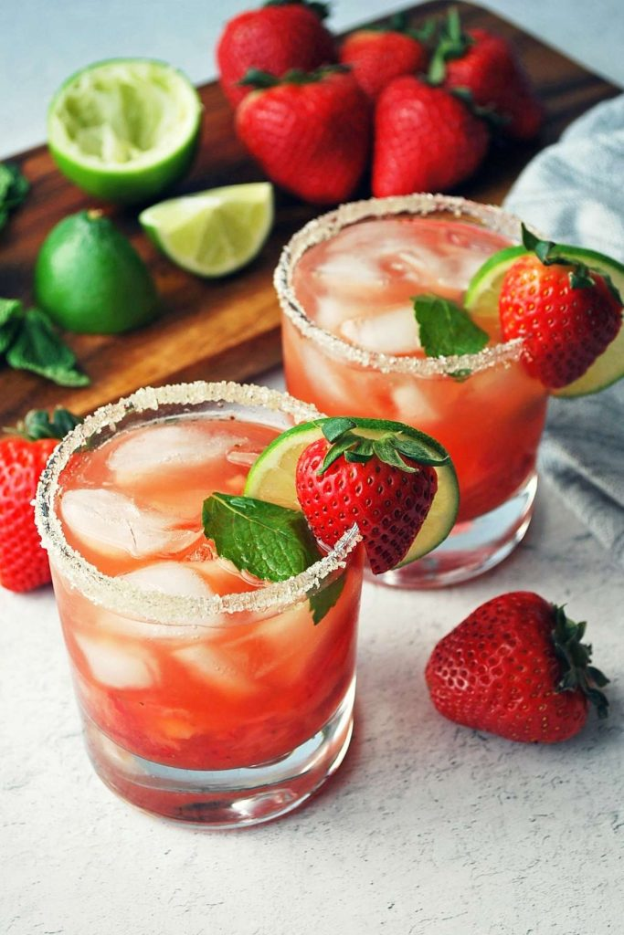 two glasses of strawberry mojitos with berries and limes in the background