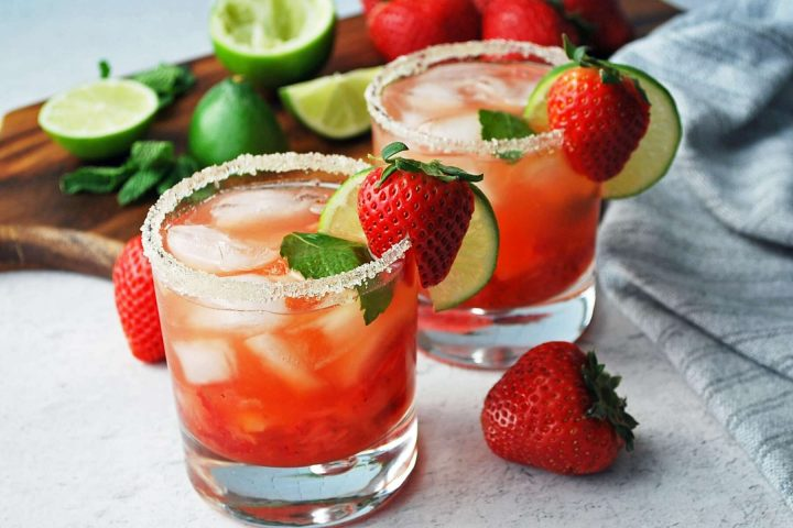 side view of two strawberry mojitos with a sugared rim and fresh lime and strawberries