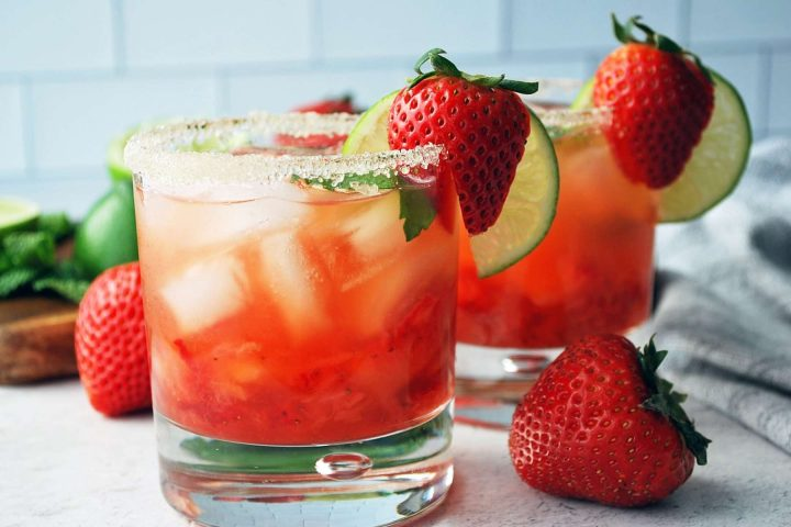 side view of glasses of strawberry mojitos with a fresh plump strawberry in front